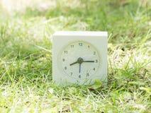Weiße einfache Uhr auf Rasenyard, 8:15 acht fünfzehn Stockfotos