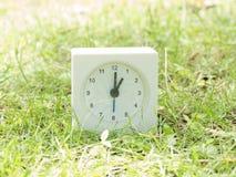 Weiße einfache Uhr auf Rasenyard, 1:00 eine O-` Uhr Stockfotografie