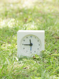 Weiße einfache Uhr auf Rasenyard, 11:45 elf fünfundvierzig Stockfotografie