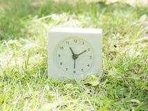 Weiße einfache Uhr auf Rasenyard, 11:10 elf zehn Stockfotografie