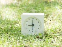 Weiße einfache Uhr auf Rasenyard, 9:00 neun O ` Uhr Lizenzfreie Stockfotografie