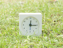 Weiße einfache Uhr auf Rasenyard, 12:15 zwölf fünfzehn Lizenzfreies Stockfoto