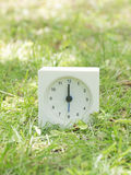 Weiße einfache Uhr auf Rasenyard, 12:00 zwölf O ` Uhr Stockfotografie