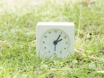 Weiße einfache Uhr auf Rasenyard, 2:05 zwei fünf Stockbild