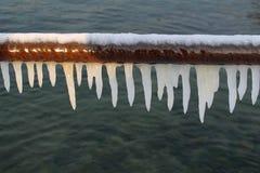 Weiße Eiszapfen auf einem Rohr stockbilder