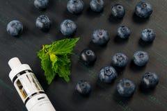 weiße elektronische Zigarette, auf einem Schwarzes gemalten Brett, nahe bei Blaubeeren und Minze Lizenzfreies Stockfoto