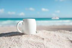 Weiße EspressoKaffeetasse mit Ozean, Strand und Meerblick lizenzfreie stockfotos