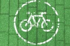 Weiße Fahrradikone auf dem grünen Ziegelsteinhintergrund, getont lizenzfreies stockbild
