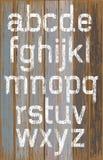Weiße Farbe des Alphabetes Farbauf hölzernem Retro- Farbhintergrund lizenzfreie abbildung