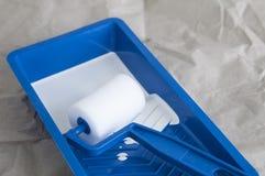 Weiße Farbe im blauen Behälter mit Farbenrolle Lizenzfreie Stockbilder