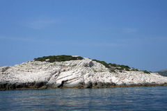 Weiße felsige Insel im Meer Stockfotografie