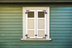 Weiße Fensterfensterläden und alte grüne hölzerne Wand Stockfoto