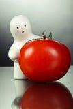 Weiße Figürchen und Tomate Stockfotografie