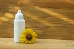 Weiße Flasche auf einem hölzernen Hintergrund Flasche und gelbe Blume Nat?rliches kosmetisches Produkt Dyal Massage des Öls Wesen stockbild