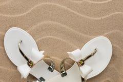 Weiße Flipflops auf dem Sand des Strandes Konzept des Restes Stockbilder
