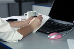 Weiße Frau übergibt Schreiben in einem Notizbuch Lizenzfreies Stockbild