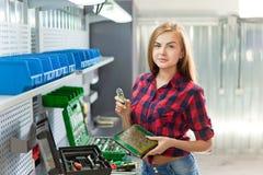 Weiße Frau des jungen Brunette mit elektronischer Platte in einer Garage Lizenzfreie Stockbilder