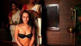 Weiße Frau, die Berufshauptbehandlung hat Indische Masseuse im Badekurortsalon stock footage