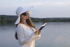 Weiße Frau im Sonnenhut las Papierbuch auf Strand Stockbilder