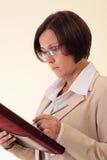 Weiße Geschäftsfrau mit Notizblock Stockfotografie