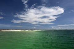 Weiße geschwollene Wolke über grünem Lagunenwasser Stockfotos