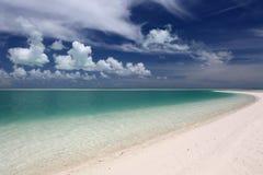 Weiße geschwollene Wolken über Türkislagunenwasser Stockbild