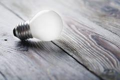 Weiße Glühlampe, die auf hölzernen Hintergrund, Ideenkonzept glüht Stockbild