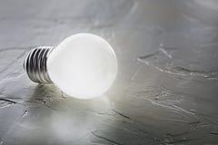 Weiße Glühlampe, die auf hölzernen Hintergrund, Ideenkonzept glüht Lizenzfreie Stockfotos