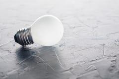 Weiße Glühlampe, die auf konkreten Hintergrund, Ideenkonzept glüht Stockfoto