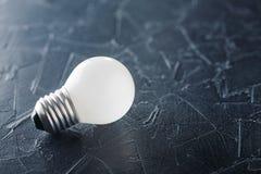 Weiße Glühlampe, die auf konkreten Hintergrund, Ideenkonzept glüht Stockbild
