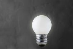 Weiße Glühlampe, die auf konkreten Hintergrund, Ideenkonzept glüht Lizenzfreies Stockfoto