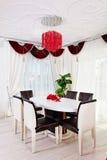Weiße glatte Tabelle mit Lederstühlen im weißen und roten classica Stockfotografie