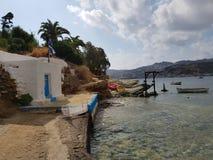 Weiße griechische Kirche auf dem Dorfkai und -boot lizenzfreies stockfoto