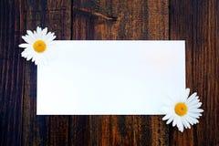 Weiße Grußkarte auf einem hölzernen Hintergrund stockfoto