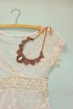 Weiße Häkelspitzespitze der Weinlese mit antiker Halskette auf hölzernem Hintergrund Stockfotografie
