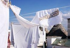 Weiße hängende Kleidung an Alberobello-Dach stockbild
