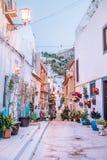 Weiße Häuser in der Mittelmeerart füllten mit Blumentöpfen am frühen Morgen stockfotos