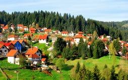 Weiße Häuser mit rot-mit Ziegeln gedecktem Dach durch Holz Stockfotografie