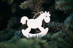 Weiße hölzerne Dekoration des Weihnachtsspielzeugs Pferdeauf dem Baum für das neue Jahr lizenzfreie stockfotos