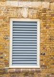 Weiße hölzerne Fensterläden in der alten Backsteinmauer Stockbild