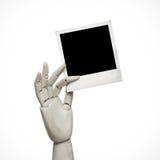 Weiße hölzerne Hand mit polaroidrahmen Stockfoto