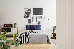 Weiße hölzerne Kommode nahe bei Bett mit dunkelblauen Kissen, grauer Daunendecke und gestreifter Schwarzweiss-Decke im Schlafzimm lizenzfreie stockfotos