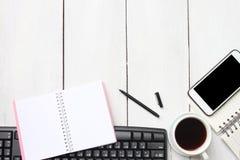 Weiße hölzerne Schreibtischtabelle der Draufsicht mit Tastatur Smartphone suppli stockfoto