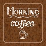 Weiße Hand gezeichnet, ` Morgen-Kaffee ` mit Holzkohle zu bewirken und Ansicht eines Tasse Kaffees auf braunem hölzernem Hintergr Stock Abbildung