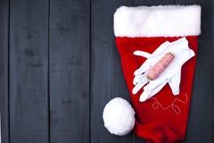 Weiße Handschuhe und eine rote Kappe mit Santa Claus-Quast Auf einem schwarzen hölzernen Hintergrund, Geschenken und Weihnachtsde lizenzfreie stockbilder