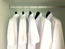 Weiße Hemden, die an den Gestellen hängen Stockfoto