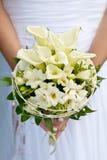 Weiße Hochzeitsblumen in den Händen der Braut Lizenzfreie Stockfotos