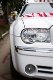Weiße Hochzeitslimousine mit Blumen Stockfotografie