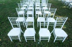 Weiße Hochzeitsstühle auf einem grünen Rasen, außen Stockfotos