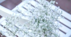 Weiße Hochzeitsstühle mit Blumen Draußen Hochzeitszeremonie Hochzeit gegründet im Garten stock video